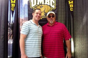 two men in front of a UMBC sign