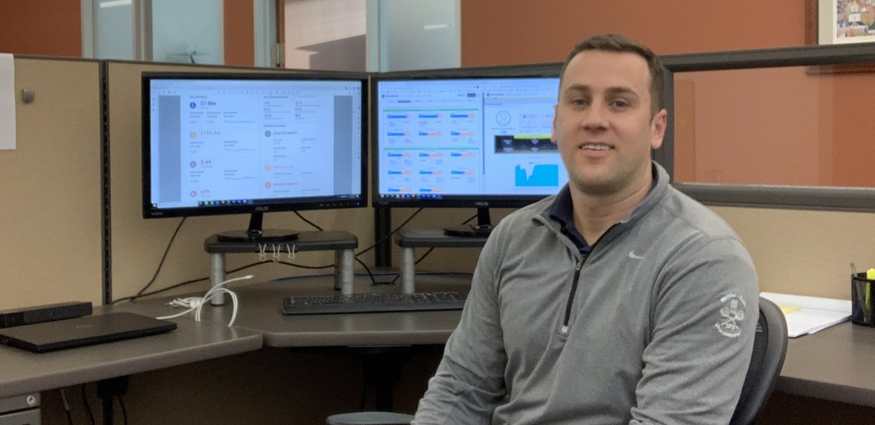 Chris Adams in office with computer screens