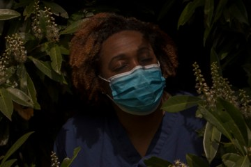 a nurse in a face mask stands in nature