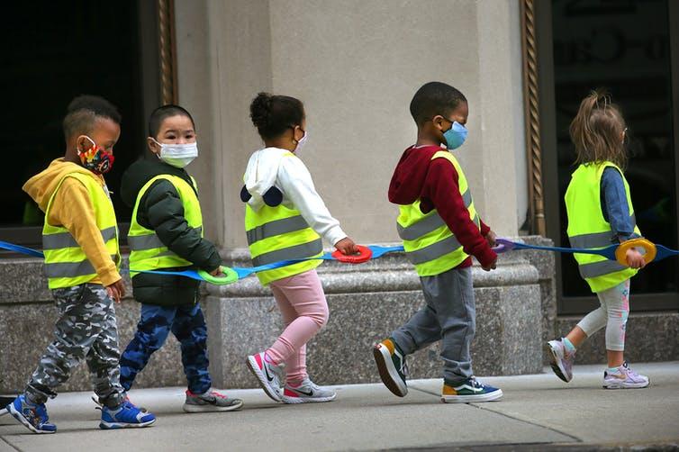 children walk in a line with masks on