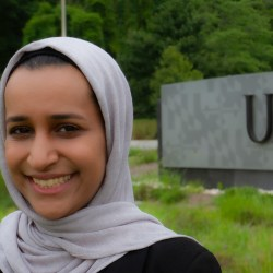 A student stands in front of UMBC sign