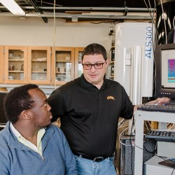 Ruben Delgado, instructs three students in his lab