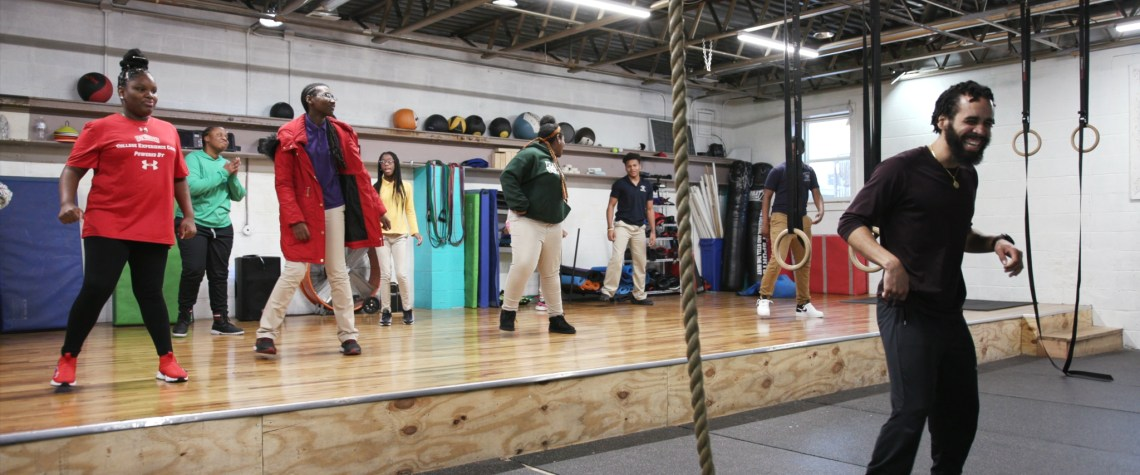 a man leads a fitness class in a gym