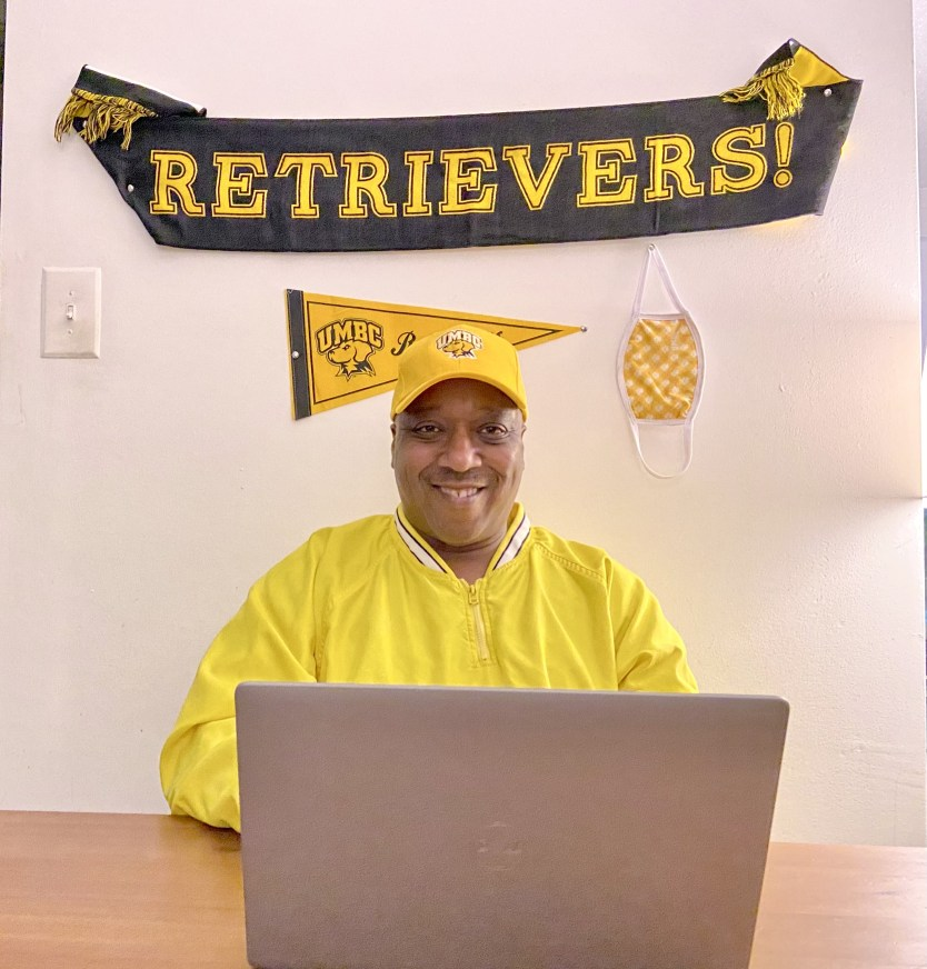 A man sits behind a laptop with a gold shirt on and a banner that says Retrievers! behind him
