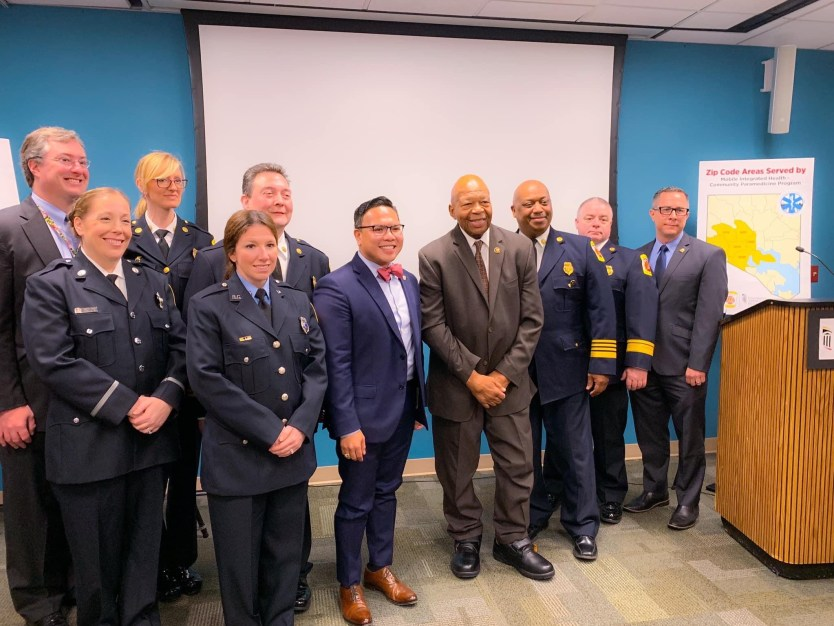 A group of men and women in paramedic uniforms take a picture together with the late Congressman Cummings