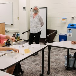 girl builds pasta model while teacher and fellow student watch