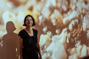 Corrie Parks standing in front of her exhibit