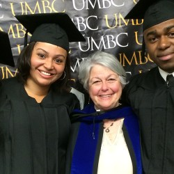 graduating students surround professor