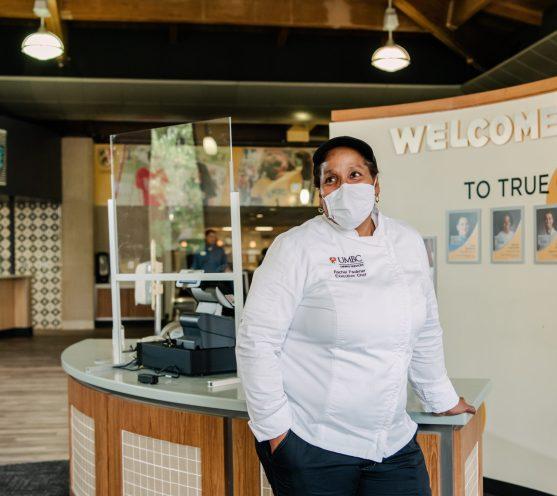 Rachel Faulkner poses next to cash register with mask