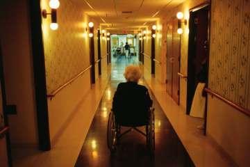 An elderly woman in a wheelchair sits alone in an empty hallway.