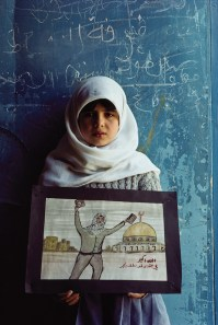 "The first story Pinneo shot for National Geographic included this photo from a Palestinian camp in Amman, Jordan, at a United Nations High Commission for Refugees school. Pinneo said, ""The girl holds up a picture of Jerusalem, a place, a homeland, she will likely never see."""