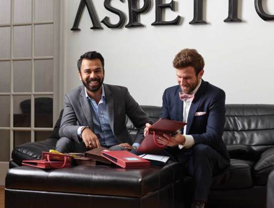 Aspetto owners Abbas Haider (left) and Rob Davis review swatch books of fabrics for the custom-made garments they sell, with and without ballistic protection. (Adam Ewing)
