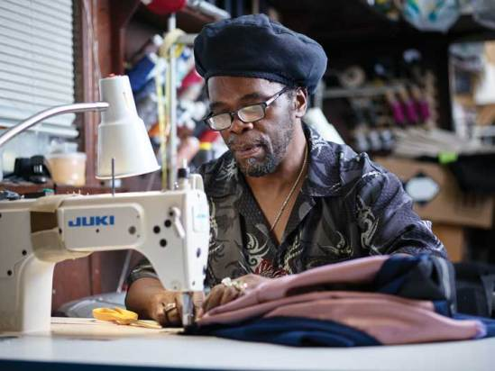 Part of the appeal of Aspetto is its well-fitting, tailor-made clothes. Here, production manager Noel McPherson machine stitches a jacket. (Adam Ewing)