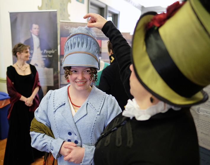 """Period dress helps make the day, including the ladies' hats, crafted by Rebecca Burnham, right. Here the milliner adjusts Megan Flanagan's """"Athena,"""" which she fashioned after the Greek goddess's helmet. (Photo by Norm Shafer)"""