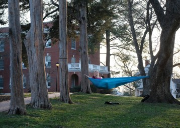 A student takes advantage of two perfectly placed trees to relax in a hammock – a favorite campus pastime. (Photo by Norm Shafer)