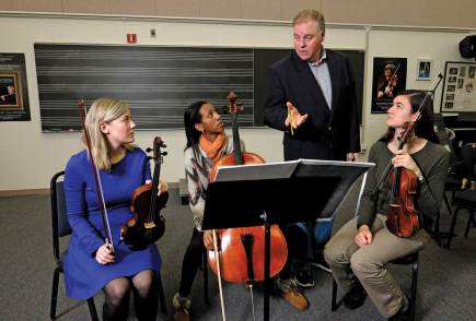 UMW Conductor Kevin Bartram rehearses with, from left, Elyse Ridder, Bethel Mahoney, and Juliette Guilloux. The student musicians contributed to the Library of Congress project. Photo by Norm Shafer.