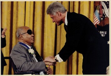 Dr. Farmer shakes hands with President Bill Clinton in 1998.