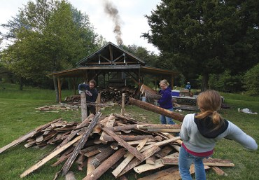A nearby sawmill provided scraps of pine and hardwoods, which students hauled, cut to length, and stacked in preparation for the first firing. They prepared much of the wood in advance but still had some to work on while the kiln heated. Pictured are Foster, Anna Moulis, and Michelle Howell.