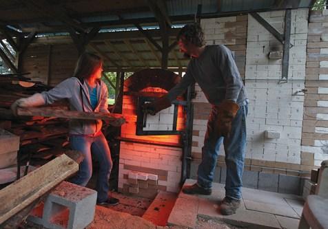 Michelle Howell stokes the kiln as Assistant Professor of Art Jon McMillan operates the firebox door.