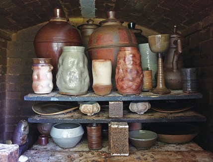 Finished works line the shelves of the kiln before unloading.