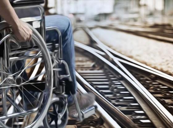 La foto mostra un disabile in carrozzina in prossimità di una rotaia