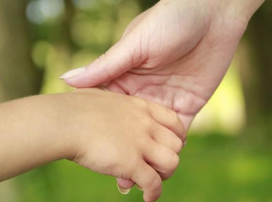 La foto mostra la mano di una mamma che stringe quella del proprio figlio