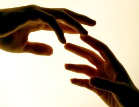 La foto mostra due mani che si sfiorano