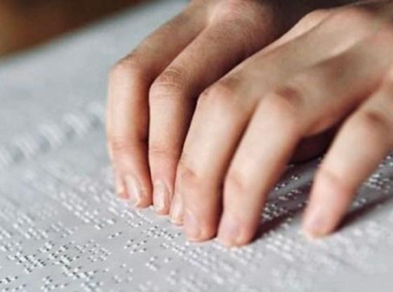 L'immagine mostra le mani di una persona non vedente che usufruisce di un testo scritto in braille