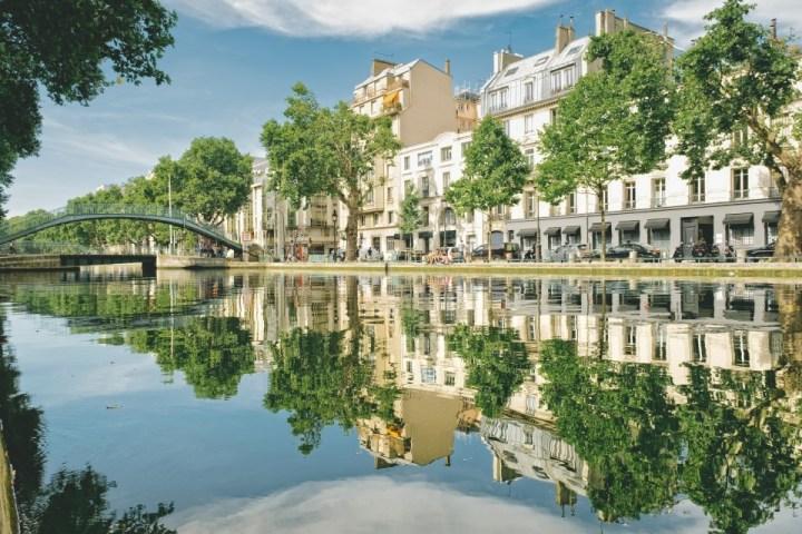 Canal Saint Martin con alberi che si riflettono sull'acqua, Parigi, Francia.