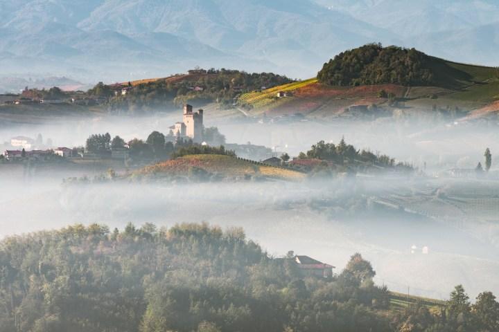 Le colline delle Langhe con dettaglio del Castello di Serralunga tra la nebbia