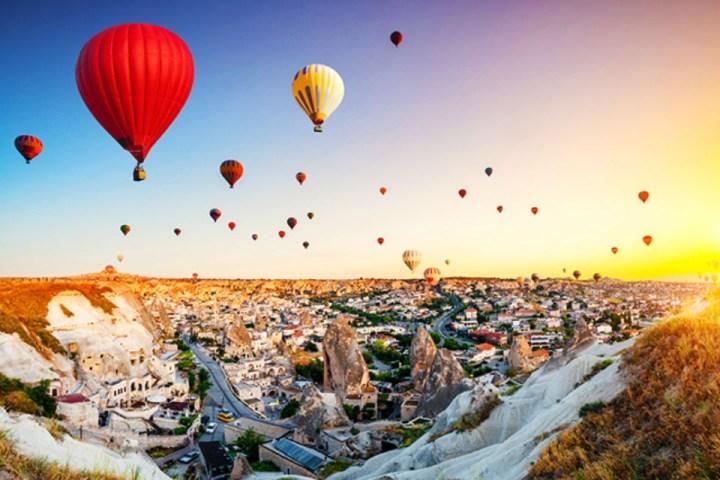 """Mongolfiere colorate sorvolano i famosi """"camini delle fate"""", formazioni rocciose tipiche dei paesaggi della Cappadocia"""