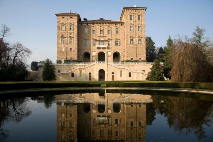 Facciata esterna del Castello Ducale di Agliè con lago in primo piano