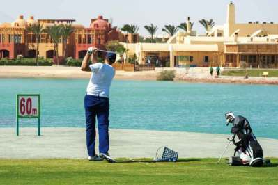 Male golfer training on a driving range