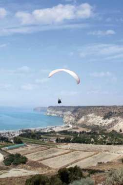 Flying paraglider in the sky, Kourion, Cyprus, a vertical picture
