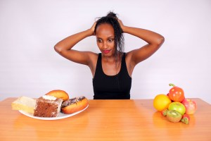 Healthy-woman-confused_Fucus Fitness_Link https www focusfitness netstock-photoswp-contentuploadsedd201707Healthy-woman-confused-with-unhealthy-foods-and-healthy-food jpg