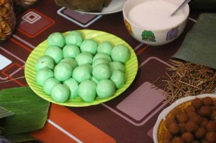 """The """"mendut"""", round cake made of rice flour, filled with shredded brown sugar inside, and covered with thick coconut milk. The green color on the mendut cakes come from """"pandan"""" leaves as natural dyes."""