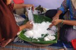 Mothers grating the coconut manually.