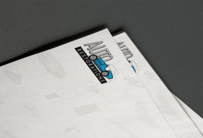 Auto Restorations letterhead, logo close-up. For Christchurch's Internationally renowned classic car restorations firm the new logo in the form of a dimensional auto makers badge, to ensure highest quality the 'AUTO' word was hand-rendered in bevelled 3D type as vector artwork. Complementing the strengthened brand on the corporate stationery a background wallpaper collage of classic auto makers brands is a web site design element that when adapted for use in print forms a design alliance between print and web Brand and identity systems design, Stationery, Illustration, Typography International classic car restoration. Brands for New Zealand companies, Christchurch, New Zealand.