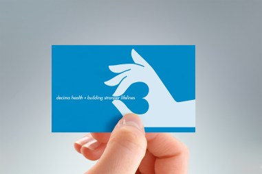 hand-held portrait of back of Decima Health business card, two colours, black and blue, two-sided card design, symbol and name on front, symbol and positioning statement illustration on back