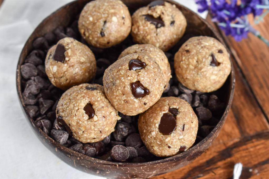 vegan cookie dough bites. the chocolate chips in the energy bites have a beautiful shine to them. The bites are served in a coconut bowl filled with chocolate chips. There are burlap sacks and purple flowers in the background.