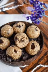 vegan cookie dough bites. one cookie dough ball has a bite out of it to show the inside texture.the chocolate chips in the energy bites have a beautiful shine to them. The bites are served in a coconut bowl filled with chocolate chips. There are burlap sacks and purple flowers in the background.