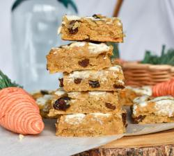 5 chickpea blondies stacked on another. All of them have icing. A glass jar and an easter basket filled with wicker carrots are in the background