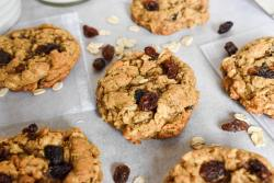 six oatmeal raisin cookies scattered over parchment paper and pretty lace bags. Close up on the cookie in the middle.Metal spatula, oats in a ramekin, and a mason jar of milk are in the background. Raisins and oats are scattered in the background as well