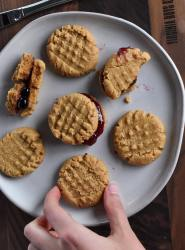 peanut butter jelly sandwich cookies on a ceramic plate. photo is focused on sandwich cookie in the middle. a broken half cookie is in the back and plain peanut butter cookies surround on the plate. Hand is reaching for a cookie