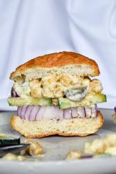"""vegan """"chicken"""" salad on a bun with red onion and cucumber and the salad layered between the two pieces of bread."""