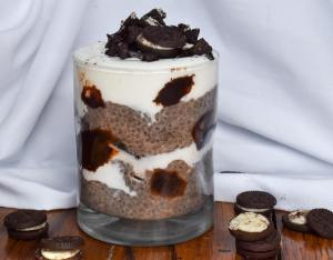 oreo chia seed pudding in a glass layered with yogurt and more oreos