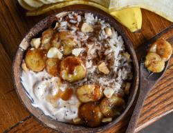 vegan breakfast bowl served in a coconut bowl filled with warmed rice, non dairy yogurt, and caramelized banana. Brown wooden table and sliced banana are shown in the background