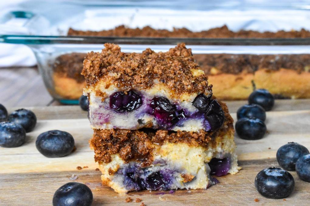 vegan blueberry coffee cake bars stacked 2 on each other with the rest in a glass pan in the background.