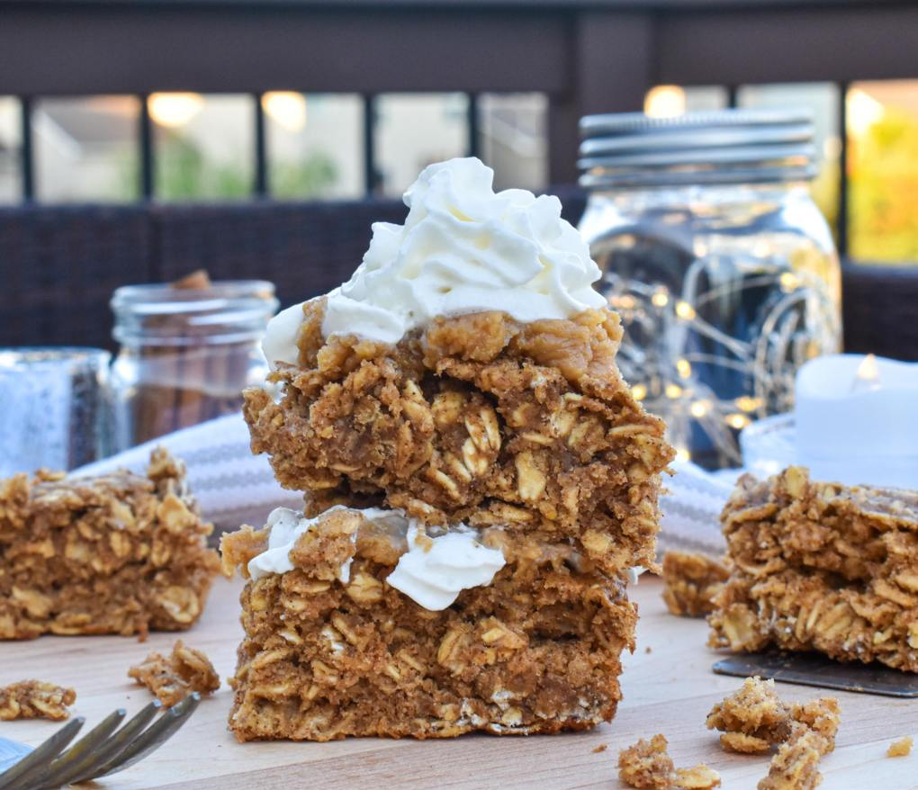 chai oatmeal breakfast bars healthy vegan gluten free breakfast recipe bars stacked on each other with cashew butter and vegan whipped cream