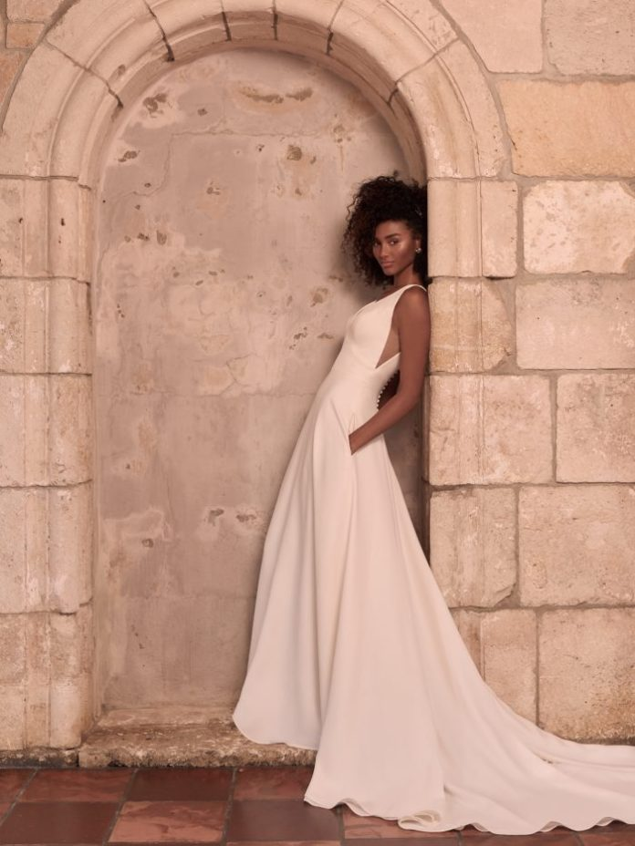 Model wears a crpe A-line wedding dress named Josephine Lynette by Maggie Sottero